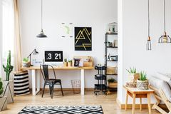 Trendy room for a freelancer. Trendy room with workspace for a freelancer with white wall, desk, black vintage chair, industrial lamps, poster and wooden sofa in Stock Photos