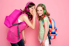 Trendy schoolgirls sharing a secret Royalty Free Stock Photos