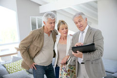 Trendy senior couple with real-estate agent visiting new house Stock Images