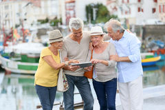 Trendy senior couples together on a trip. Senior couples looking at map on traveling journey stock image