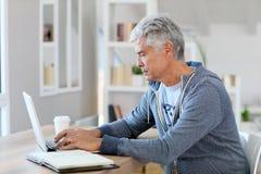 Trendy senior man using laptop at home Stock Photo