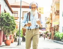Free Trendy Senior Man Using Music Smartphone App And Drinking Coffee In Downtown Center Outdoor - Mature Fashion Male Having Fun With Stock Photo - 169960350
