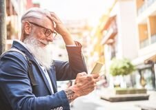 Free Trendy Senior Man Using Smartphone App In Downtown Center Outdoor - Mature Fashion Male Having Fun With New Trends Technology - Royalty Free Stock Photo - 169960235
