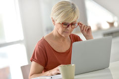 Trendy senior woman at home working on laptop Stock Photography