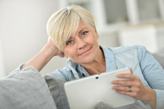 Trendy senior woman using tablet at home Royalty Free Stock Image
