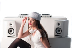 Trendy sexy DJ dressed in white mixing music Royalty Free Stock Images