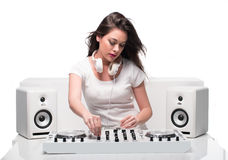Trendy sexy DJ dressed in white mixing music Royalty Free Stock Photos