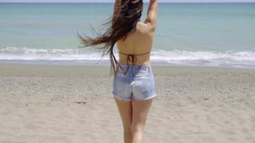 Trendy shapely young woman standing on a each. In her bikini top and a skimpy pair of denim shorts laughing as she looks to the side stock video