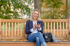 Trendy smiling blond woman using her mobile royalty free stock images