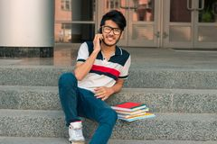 Smiling young guy sits on a street with books and talking on the phone stock image