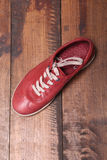 Trendy sport shoes on a wooden surface. Trendy red sport shoes on a wooden surface Stock Photos