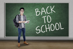 Trendy student back to school and use tablet. Portrait of male high school student back to school and standing in the classroom while using a digital tablet Stock Photography