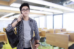 Trendy student speaking on the phone. Potrait of trendy student carrying backpack and speaking on the phone, shot in the classroom Royalty Free Stock Photo