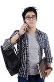 Trendy student talking on the phone. Portrait of asian student talking on the phone, isolated over white background Royalty Free Stock Images