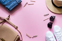 Trendy stylish female clothes flatlay. Jeans, sneakers, round sunglasses, gold hair clip, bag and hat. Pink background. royalty free stock image