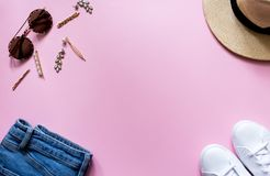 Trendy stylish female clothes flatlay. Jeans, white sneakers, round sunglasses, gold hair pins and hat, pink background. stock photo
