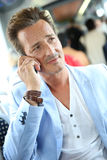Trendy stylish man in tramway talking on the phone Royalty Free Stock Photography