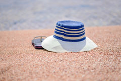 Trendy sunhat and beach thongs on the sand. Trendy sunhat and beach thongs or slip slops lying on the golden sand of a tropical beach in the summer sun Stock Image