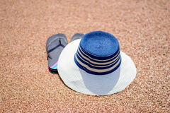 Trendy sunhat and beach thongs on the sand. Trendy sunhat and beach thongs or slip slops lying on the golden sand of a tropical beach in the summer sun Royalty Free Stock Photos