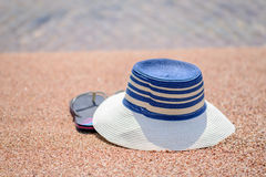 Trendy sunhat and beach thongs on the sand. Trendy sunhat and beach thongs or slip slops lying on the golden sand of a tropical beach in the summer sun Royalty Free Stock Image