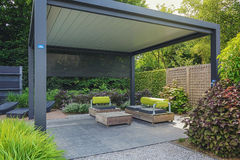 Trendy sunloungers and overhang with trendy garden furniture. Royalty Free Stock Images