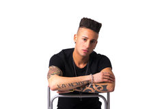 Trendy tattooed young man sitting on chair backwards Stock Images
