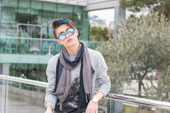 Trendy teen boy outdoors. Young man stands on a city street with sunglasses Stock Image