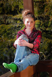 Trendy Teen Girl. A pretty trendy teenage girl sitting on a sunny wooden deck railings wearing a red plaid shirt and grunge pants with torn holes.  Shallow depth Stock Image