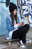 Trendy teenager with smartphone and skateboard Royalty Free Stock Photo