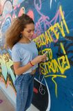 Trendy teenager using a smartphone. An happy teenager using her brand new smartphone is leaning against a graffiti wall Royalty Free Stock Photo