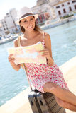 Trendy tourist woman sitting on suitcase checking city map Royalty Free Stock Photos