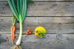 Trendy ugly vegetables on barn wood. Trendy ugly organic carrot, tomatos, ugly lemon and leek from home garden bed on barn wood table, Australian grown Stock Photo