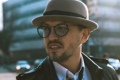 Trendy unshaven man in a hat and glasses looking aside Stock Photos