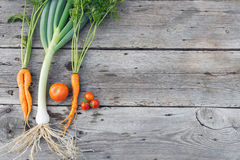 Trendy vegetables on barn wood. Trendy organic carrot, tomatos and leek from home garden bed on barn wood table, Australian grown Royalty Free Stock Photo
