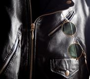 Trendy vintage circle sunglasses in a pocket of a studded jacket. Trendy vintage circle sunglasses in a pocket of a black studded  jacket Stock Images