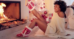 Trendy vivacious woman wearing Christmas booties. Warming her feet in front of a blazing fire as she sits on the floor alongside the tree and pile of gifts stock footage