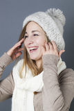 Trendy warm winter,woman. Trendy warm winter - giggling young blond girl getting warmer with white wool winter scarf and hat enjoying softness and comfy fashion Royalty Free Stock Image