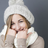 Trendy warm winter,woman. Trendy warm winter - laughing young blond girl getting warmer with white wool winter scarf and hat enjoying softness and comfy fashion Stock Photography