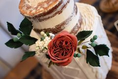 Trendy wedding cake with edible rose floral arrangement. Cake features a naked top tier with a knitted design bottom tier royalty free stock photos