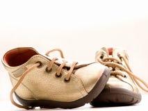 Trendy weinig gouden babyschoenen met copyspace Stock Afbeelding