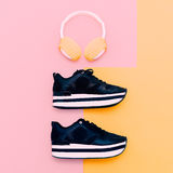 Trendy white headphones and sneakers on vanilla background. Stock Image