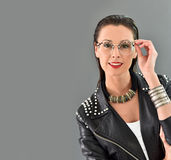 Trendy woman with accessories. Beautiful trendy woman with eyeglasses, grey background Stock Images