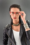 Trendy woman with accessories. Beautiful trendy woman with red eyeglasses, grey background Stock Images