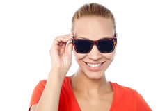 Trendy woman adjusting her sunglasses Royalty Free Stock Photos