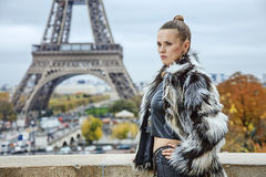 Trendy woman against Eiffel tower in Paris looking into distance Royalty Free Stock Images