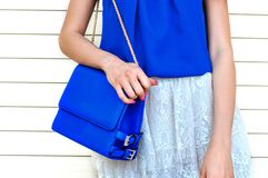 Trendy woman in blue blouse and white lace skirt holding small blue leather bag w. Fashionable and luxury style elegant female bag. Trendy woman in blue blouse Stock Photography