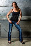 Trendy Woman in blue jeans posing in the grungy underground Stock Images