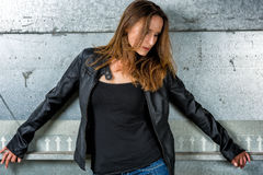 Trendy Woman in blue jeans posing in the grungy underground. Trendy Woman with long hair in blue jeans posing in the grungy underground Stock Photo