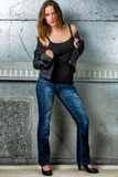 Trendy Woman in blue jeans posing in the grungy underground Royalty Free Stock Image