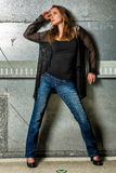 Trendy Woman in blue jeans posing in the grungy underground Royalty Free Stock Images